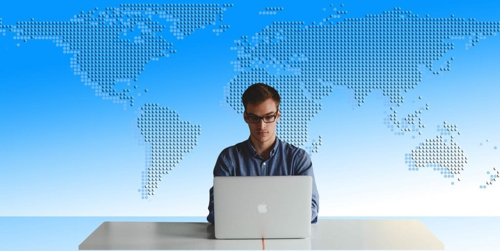 man sitting at a table using a computer with a map of the world in the background